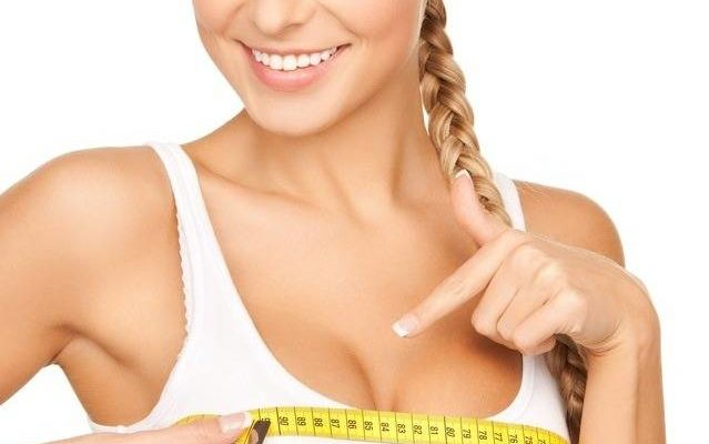 picture of young beautiful woman measuring her breast
